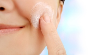 Woman rubbing a facial scrub on her skin