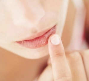 Woman applying lip scrub to her lips