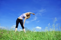 Woman stretching in a field of green grass